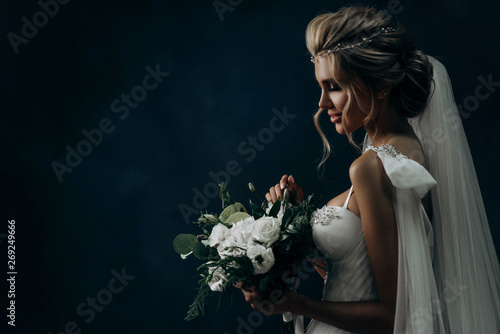 Foto auf Leinwand Friseur portrait of a luxurious bride on a dark background. Model with a beautiful make-up and hairstyle