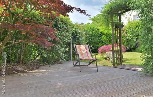 deck chair on a wooden terrace in a landscaped garden Fototapete