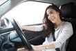 Young Asian woman driving her car and fasten seat belt with glad positive expression during the drive to travel journey, Relaxed smile happy woman on road trip vacation concept