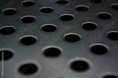 Foto op Plexiglas Kikker Gray monophonic background with big quantity of holes in a metal plate. Surface. Texture.