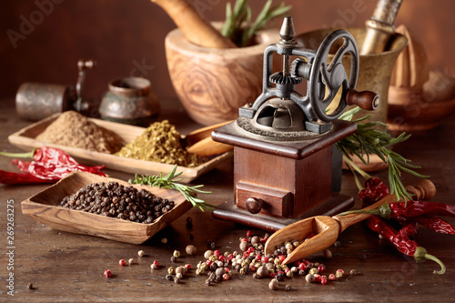Canvas Print Vintage pepper mill with kitchen utensils, spices and rosemary on a old wooden table