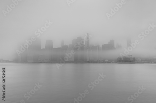 Photo Stands New York Financial district covered in fog from east river in black and white photo
