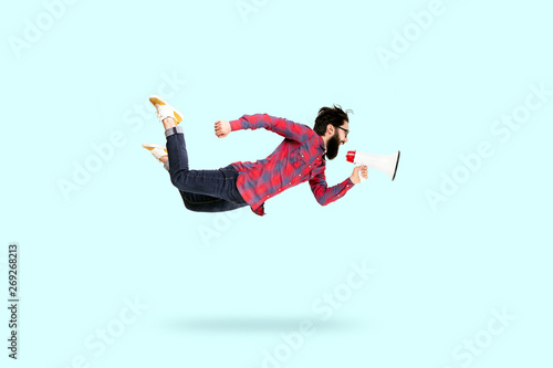 Canvas Print Bearded hipster man in glasses, jumping and shouting in megaphone, photo over bl