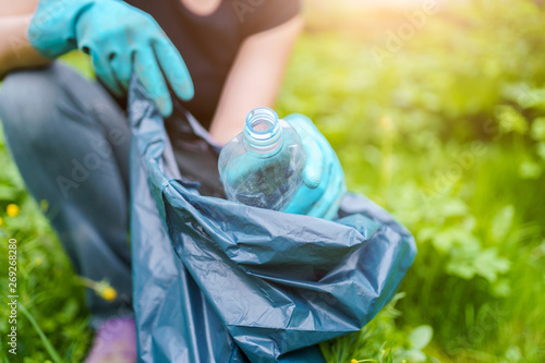 Photo of woman in rubber gloves picking up dirty plastic bottle in bag on green Canvas-taulu