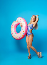 Full-length Photo Of Woman In Striped Swimsuit With Life Preserver Donut On Blue Empty Background