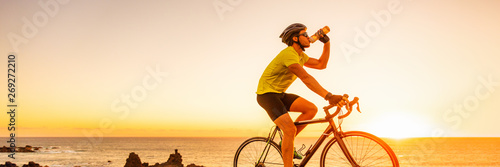 Photo Triahtlon athlete man drinking water bottle on road racing bike ride outdoors at sunset banner panorama landscape