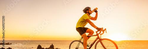 Fotografia Triahtlon athlete man drinking water bottle on road racing bike ride outdoors at sunset banner panorama landscape