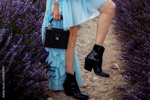 Fototapeta On a beautiful girl details of a blue dress, black boots and a black bag on the background of lavender obraz