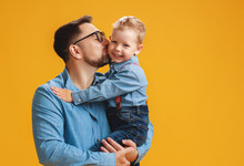 Happy Father's Day! Cute Dad And Son Hugging On Yellow Background