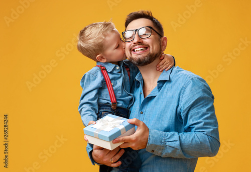 Photo  happy father's day! cute dad and son hugging on yellow background