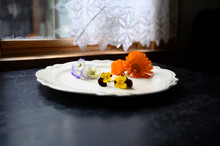 Edible Flowers Arranged On A White Plate By A Window