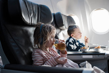 Blonde Girl Drinking And Listening To Music On A Plane Watching Tv