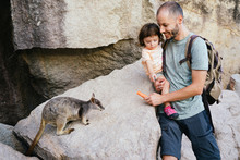Father And Toddler Daughter Feeding A Wallaby With Carrot In Australia