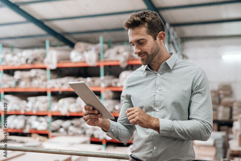 Fototapeta Smiling manager standing in his warehouse using a digital tablet