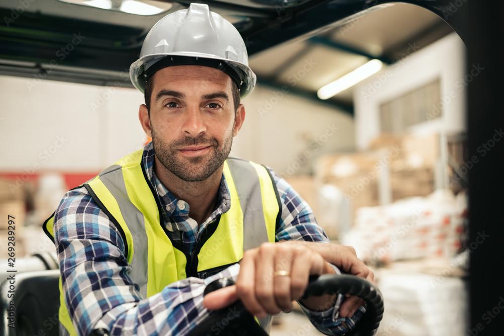 Fototapeta Smiling warehouse worker sitting in a forklift