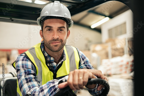 Fotografía  Smiling warehouse worker sitting in a forklift