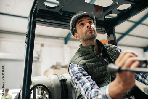 Fotomural  Forklift driver carefully moving stock around in a warehouse