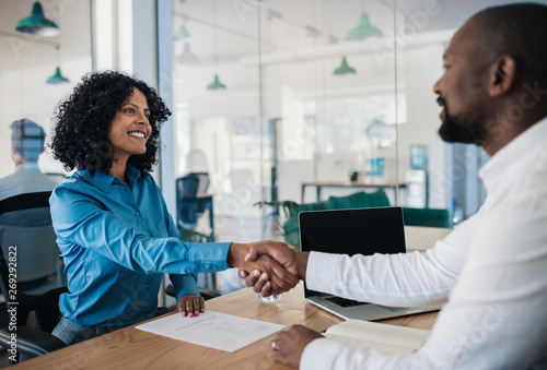 Smiling manager shaking hands with a woman after an interview Canvas Print