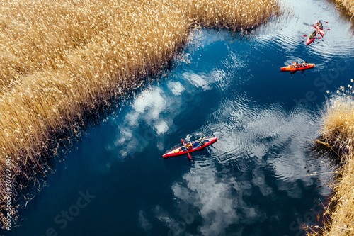 Group of people in kayaks among reeds on the autumn river. Tablou Canvas