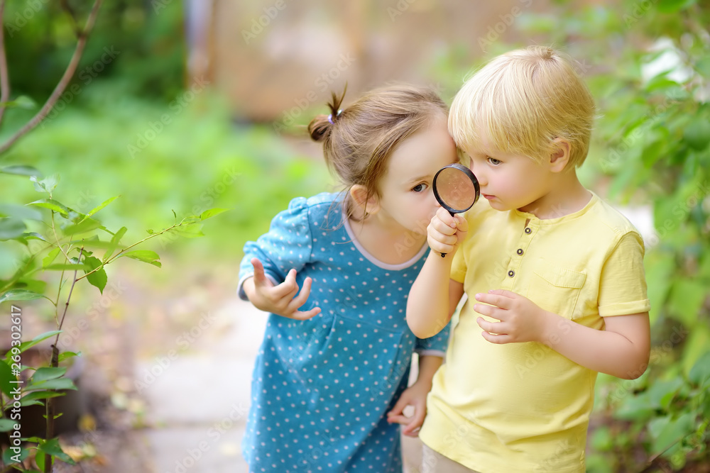 Fototapety, obrazy: Kids exploring nature with magnifying glass. Close up. Little boy and girl looking with magnifying glass