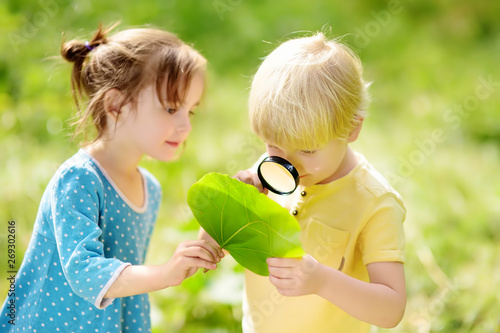 Fototapeta Kids exploring nature with magnifying glass. Close-up. Little boy and girl looking on leaf with magnifier. obraz