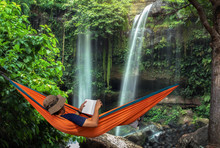 Man Lying In A Hammock In Forest And Enjoying A Book Reading. Man By The Waterfall Hanging On Hammock Relaxing In The Morning