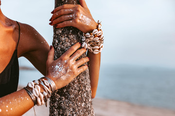 close up of young woman hands wearing boho accessories made of cowry shells