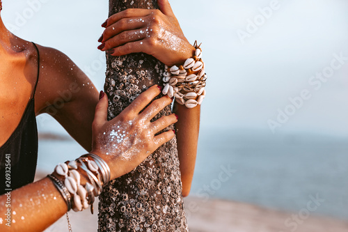 Leinwand Poster close up of young woman hands wearing boho accessories made of cowry shells