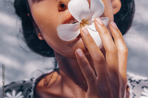 close up of beautiful young woman holding frangipani flower in mouth Fototapete