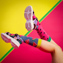 Concept Of Merry Summer Mood, Relaxation And Beauty. Female Legs In White Sandals And Bright Color Different Socks With A Watermelon Print And Seeds On An Isolated Bright Pink, Yellow, Blue Background