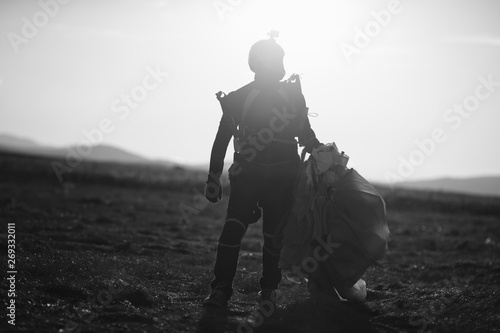 Fotografia Silhouette skydiver with a parachute in the hands of a person walking on the field after landing, close-up