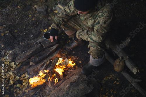 Fotografie, Obraz Man in camouflage drinking tea and warms himself by the fire in bad weather