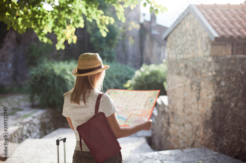 Foto  Woman traveler is looking at city map at town street in Europe