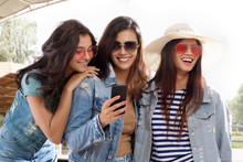 Three Girl Friends Standing Together Looking At Mobile Phone
