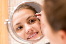 Beautiful Woman With Tweezers Is Plucking Eyebrows While Looking Into The Mirror In Bathroom. Beauty Skincare And Wellness Morning Concept