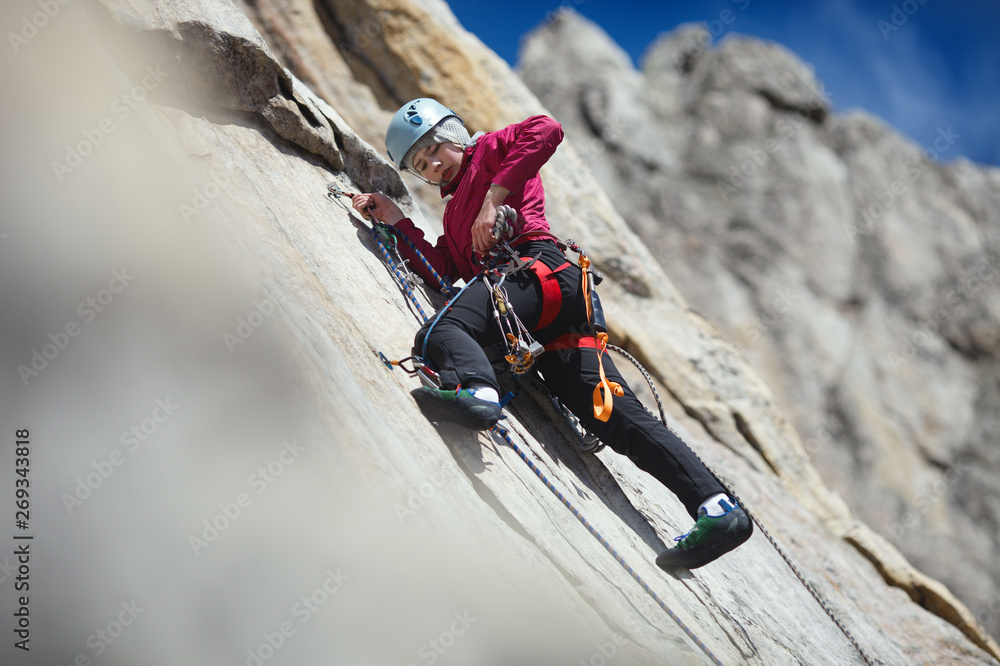 Fototapety, obrazy: Young woman is engaged in rock climbing in the mountains. Sport climbing.
