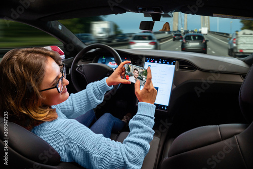 Woman communicates by video call while her car is driven by an autopilot. Self driving and autonomous vehicle concept