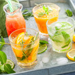Assorted summer cold citrus drinks on a metal tray, square