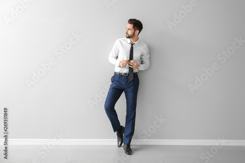 Fotografia  Fashionable young man near grey wall
