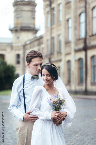 The first walk of the newlyweds, walking hug, love each other. girl in her hands holding flowers