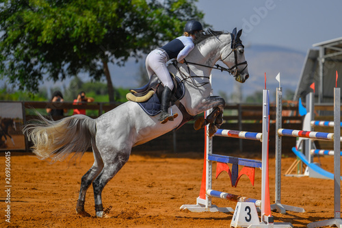 Acrylic Prints Horseback riding Young rider jumping over the obstacles during the horse jumping competition