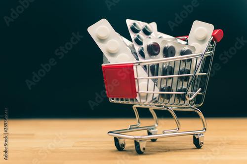 Photo  A miniature shopping cart full of pills.