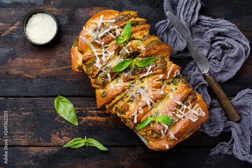 Foto op Aluminium Aap Pull-apart bread with Italian pasta pesto, basil and parmesan cheese in baking form over old wooden background. Top view. Rustic stile.