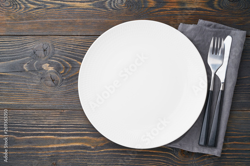 Fotografie, Obraz  clean empty white plate, fork and knife on dark rustic wooden table, copy space, mock up, top view