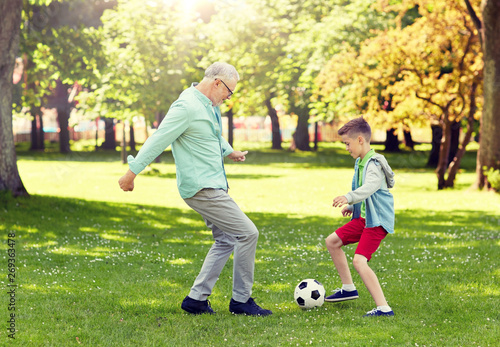 Obraz family, generation, game, sport and people concept - happy grandfather and grandson playing football at summer park - fototapety do salonu