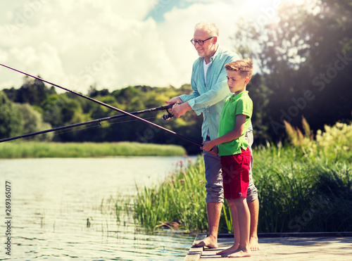Poster Peche family, generation, summer holidays and people concept - happy grandfather and grandson with fishing rods on river berth