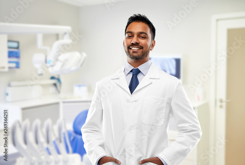 medicine, dentistry and profession concept - smiling indian male dentist in white coat over dental clinic office background