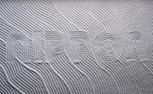 Japanese Zen Garden Raked With The Word NIPPON (English Translation: Japan) In Capital Letters In Textured White Sand
