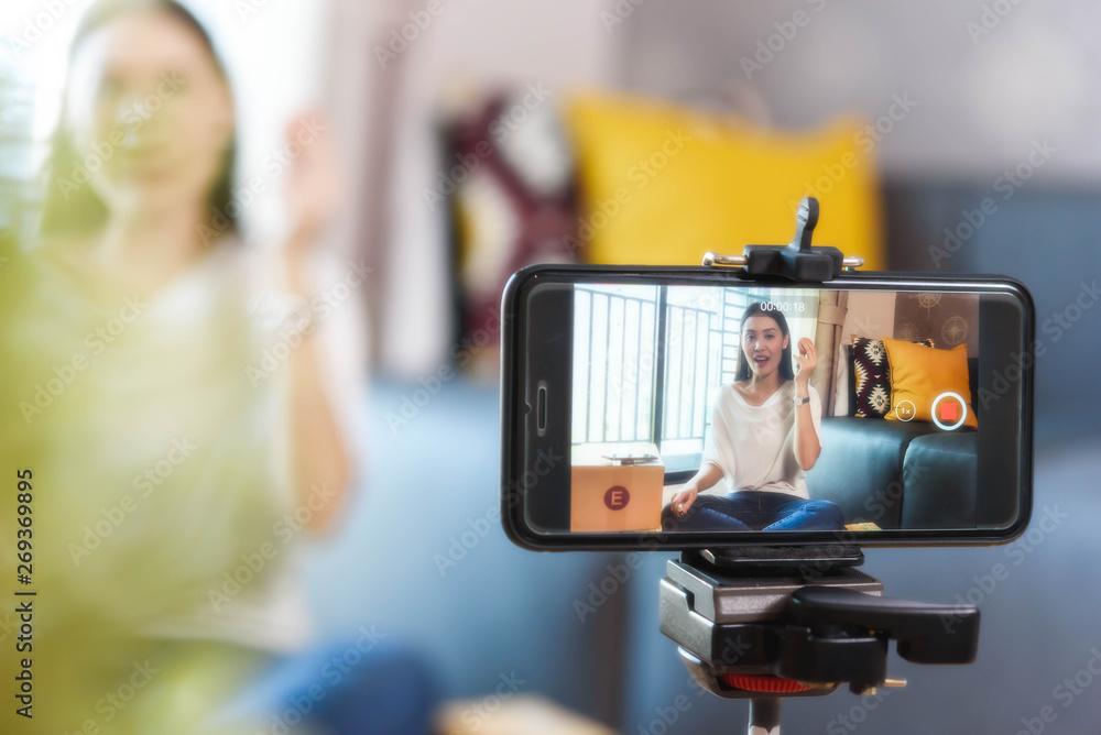 Fototapeta Beauty blogger demonstrating how to make up and review products on live broadcast use smartphone, life of an influencer