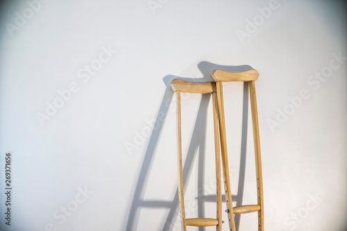 Vászonkép crutches stand at the light wall as a symbol of disability and injury